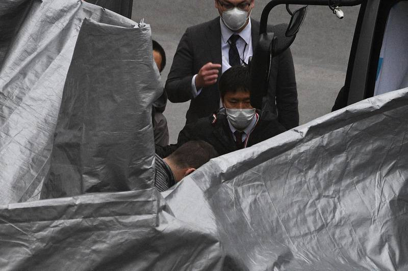 A man (bottom-C) believed to be US citizen Peter Taylor, who allegedly helped his father Michael to stage an operation to fly former Nissan chief Carlos Ghosn out of Japan in 2019, gets on a bus after arriving at Narita airport in Chiba prefecture on March 2, 2021 following his extradition from the US. (Photo by Kazuhiro NOGI / AFP)