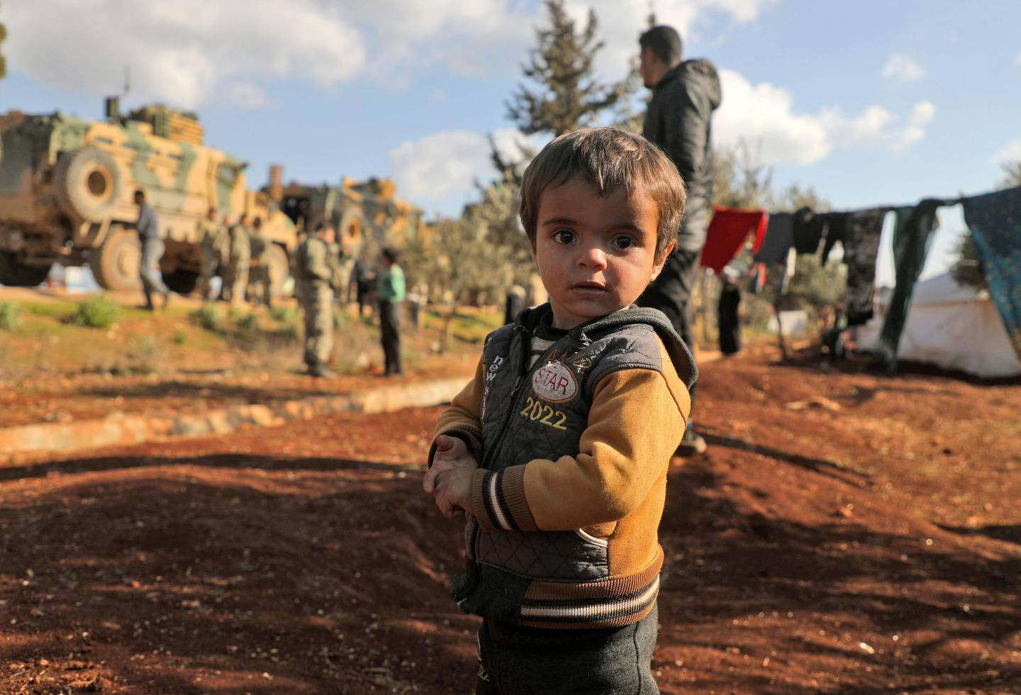 A displaced Syrian child looks to the camera as Turkish soldiers gather near the town of Batabu on the highway linking Idlib to the Syrian Bab al-Hawa border crossing with Turkey, on March 2, 2020. The Syrian government pledged to repel Turkish forces attacking its Russia-backed troops in northwestern Syria as tensions spike between Damascus and Ankara. Since December, Syrian regime forces have led a deadly military offensive against the last major opposition stronghold of Idlib, where Turkey supports some rebel groups. Damascus said it shot down three Turkish drones in the region the day before, while two Syrian warplanes were downed though the pilots escaped unharmed. / AFP / AAREF WATAD