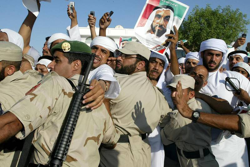 Emirati policemen control the crowd during the funeral of Sheikh Zayed bin Sultan al-Nahayan (seen in portrait) in Abu Dhabi 03 November 2004. Nahayan, the president and founding father of the United Arab Emirates, died 02 November 2004 after more than 30 years at the helm of his oil-rich country.      AFP PHOTO/RABIH MOGHRABI / AFP PHOTO / RABIH MOGHRABI