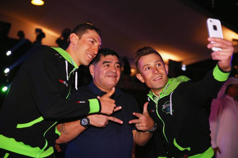 DUBAI, UNITED ARAB EMIRATES - FEBRUARY 03:  Stefano Pirazzi (l) and Nicola Ruffoni (r) of Italy and Bardiani CSF take a selfie with Diego Maradona at the opening ceremony of the Dubai Tour on February 3, 2015 in Dubai, United Arab Emirates.  (Photo by Bryn Lennon/Getty Images)