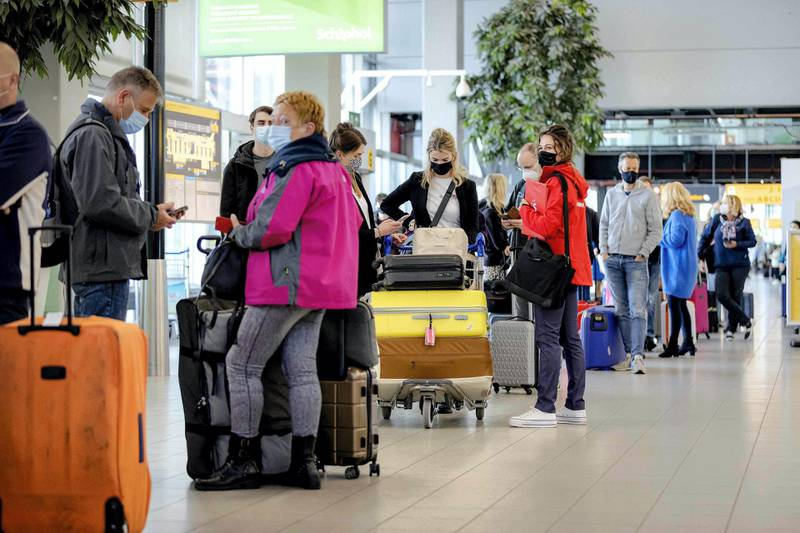Holidaymakers queue as they leave from Schiphol airport in Amsterdam for a test holiday on April 12, 2021, amid the Covid-19 pandemic. The aim is to see whether a test protocol makes it possible to travel despite the Covid-19 pandemic. - Netherlands OUT  / AFP / ANP / ROBIN VAN LONKHUIJSEN