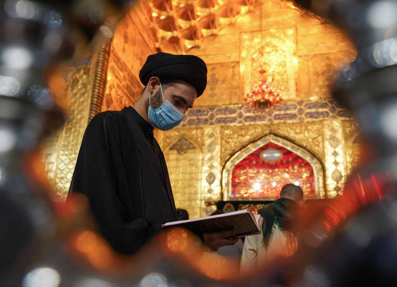 A Shiite cleric reads the Koran, Islam's holy book, during prayer rituals of Laylat al-Qadr (Night of Destiny) which marks the night in which the holy Koran was first revealed to the Prophet Mohammed, at the Imam Ali shrine in the Iraqi city of Najaf, on May 1, 2021. / AFP / Ali NAJAFI