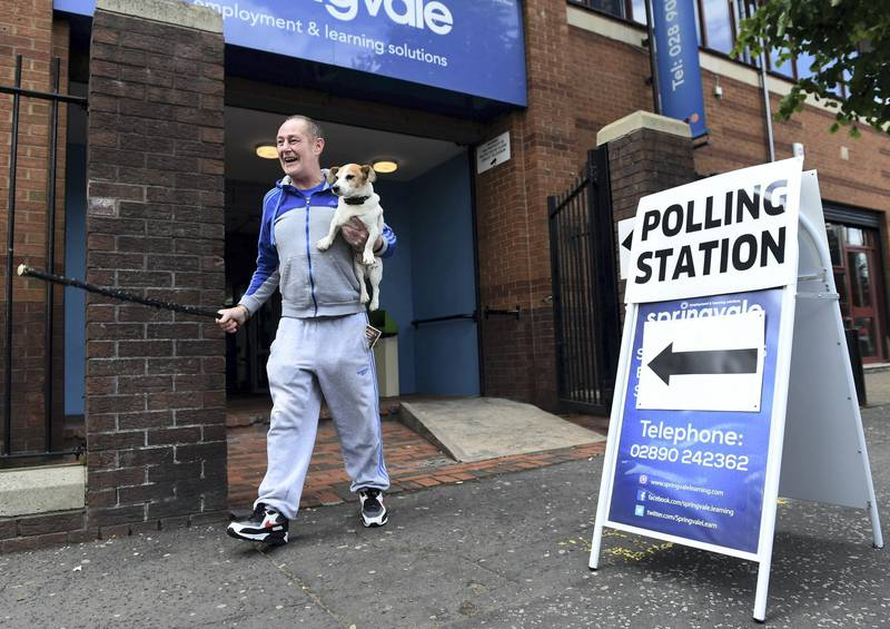 BELFAST, NORTHERN IRELAND - JUNE 23: A man accompanied by his dog laughs as he exits a polling station after voting in the EU referendum on June 23, 2016 in Belfast, Northern Ireland. The United Kingdom has gone to the polls to decide whether or not the country should remain within the European Union (EU). After a closely fought campaign from both the REMAIN and LEAVE campaigns the vote is considered too close to call. Counting will commence once the polls close later on Thursday with a result on the referendum expected on Friday morning. (Photo by Charles McQuillan/Getty Images)