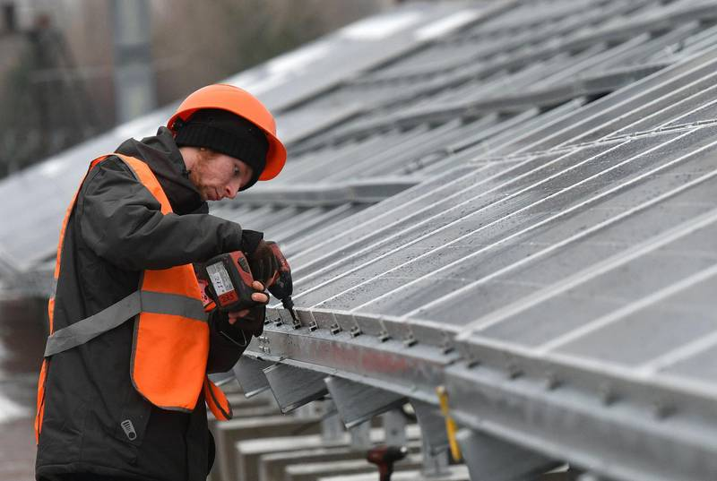 """A worker installs photovoltaic panels on the new one-megawatt power plant next to the New Safe Confinement over the fourth block of the Chernobyl nuclear plant on December 12, 2017. At ground zero of Ukraine's Chernobyl tragedy, workers in orange vests are busy erecting hundreds of dark-coloured panels as the country gets ready to launch its first solar plant to revive the abandoned territory. The new one-megawatt power plant is located just a hundred metres from the new """"sarcophagus"""", a giant metal dome sealing the remains of the 1986 Chernobyl accident, the worst nuclear disaster in the world. """"This solar power plant can cover the needs of a medium-sized village"""", or about 2,000 flats, Yevgen Varyagin, the head of the Ukrainian-German company Solar Chernobyl which carried out the project, told AFP. / AFP PHOTO / Genya SAVILOV"""