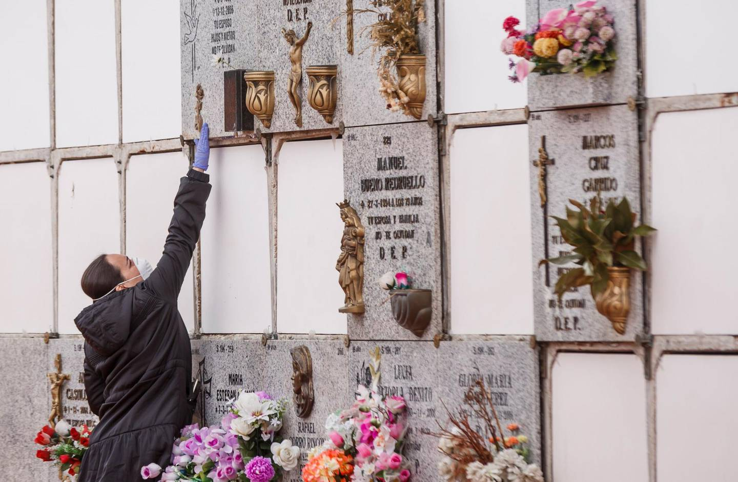 A woman wearing a face mask and gloves touches a niche during the burial of a man who died of the new coronavirus at the South Municipal cemetery in Madrid, on March 23, 2020. The coronavirus death toll in Spain surged to 2,182 after 462 people died within 24 hours, the health ministry said. The death rate showed a 27-percent increase on the figures released a day earlier, with the number of confirmed cases of COVID-19 rising to 33,089 in Spain, one of the worst-hit countries in the world after China and Italy.  / AFP / BALDESCA SAMPER