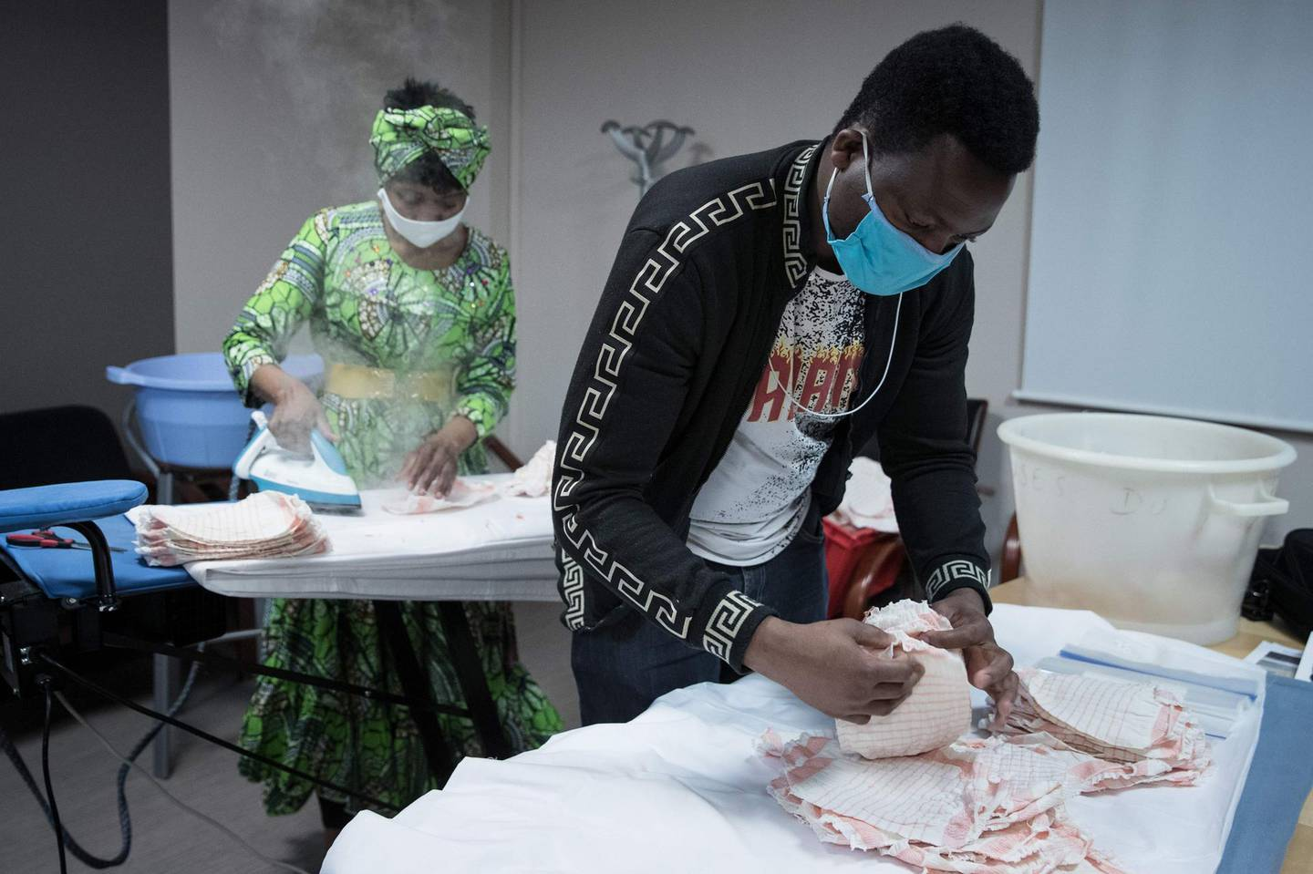 Undocumented immigrants Cameroonian Florence irons home made protective facemasks for The Salvation Army (Armee du Salut) charitable organisation, in Paris, on April 6, 2020, on the twenty-first day of a strict lockdown in France to stop the spread of COVID-19 (novel coronavirus).  / AFP / JOEL SAGET