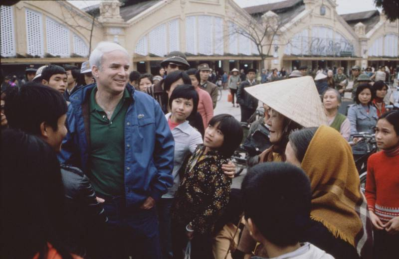 American politician Senator John McCain (center, in blue jacket and green shirt) talks with people on a crowded street during the filming of a CBS Reports Special entitled 'Honor, Duty and a War Called Vietnam,' Hanoi, Vietnam, March 6, 1985. (Photo by CBS Photo Archive/Getty Images)