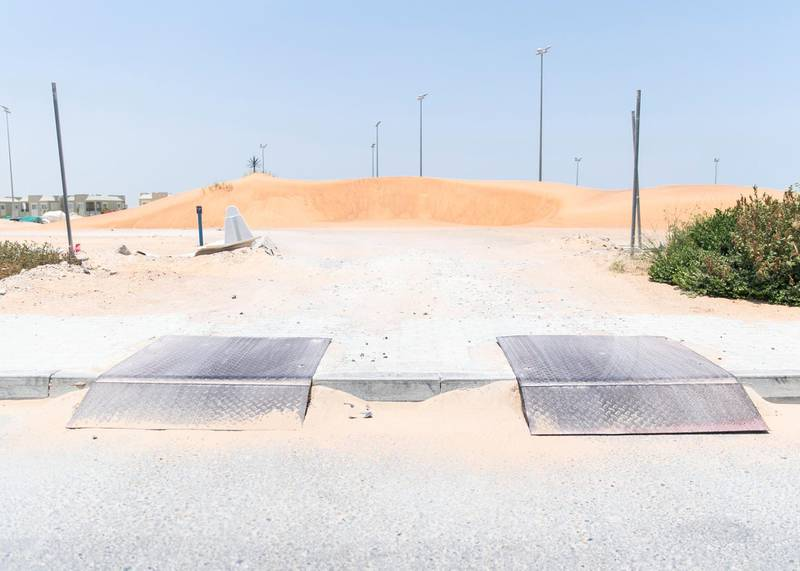 DUBAI, UNITED ARAB EMIRATES - JULY 15 2019.Residents use unpaved roads to access their villas at Living Legends.Some residents and investors of Living Legends have paid Dh6m for villas, and pay Dh25,000 a year in service charges but the development still looks like a construction site, with an unfinished golf course, roads, open sewer works near the school, poor lighting and no desert boundary meaning dangerous snakes and animals are regularly getting into the gardens and villas. (Photo by Reem Mohammed/The National)Reporter: NICK WEBSTERSection: NA