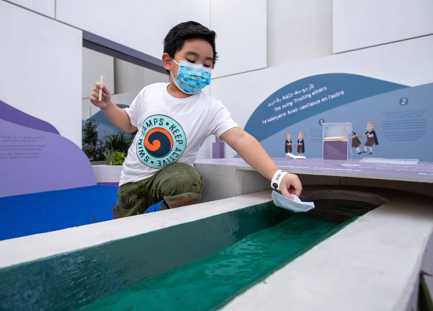 Louvre Abu Dhabi Children's Museum reopens this week. Preview/tour of the revamped space June, 15, 2021. Jacob Morella, 4, launches his paper boat at the garden area of the exhibition. Victor Besa / The National. Reporter: Alexandra Chaves for Arts & Culture.