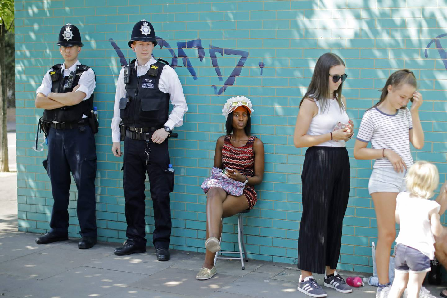 Police officers keep an eye out on the first day of the Notting Hill Carnival in west London on August 27, 2017.  Nearly one million people are expected by the organizers Sunday and Monday in the streets of west London's Notting Hill to celebrate Caribbean culture at a carnival considered the largest street demonstration in Europe. / AFP PHOTO / Tolga AKMEN