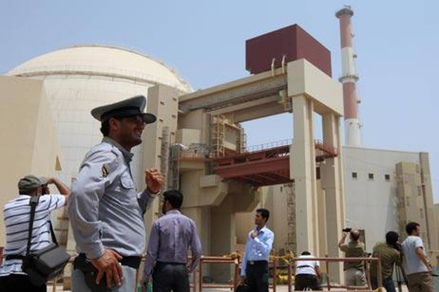"""(FILES) -- An Iranian security man stands next to journalists outside the reactor building at the Russian-built Bushehr nuclear power plant in southern Iran on August 21, 2010. The Stuxnet computer worm has infected 30,000 computers in Iran but has failed to """"cause serious damage,"""" Iranian officials were quoted as saying on September 26, 2010. A German computer security researcher suspected Stuxnet's target was the Bushehr nuclear facility in Iran, where unspecified problems have been blamed for getting the facility fully operational. AFP PHOTO/ATTA KENARE"""