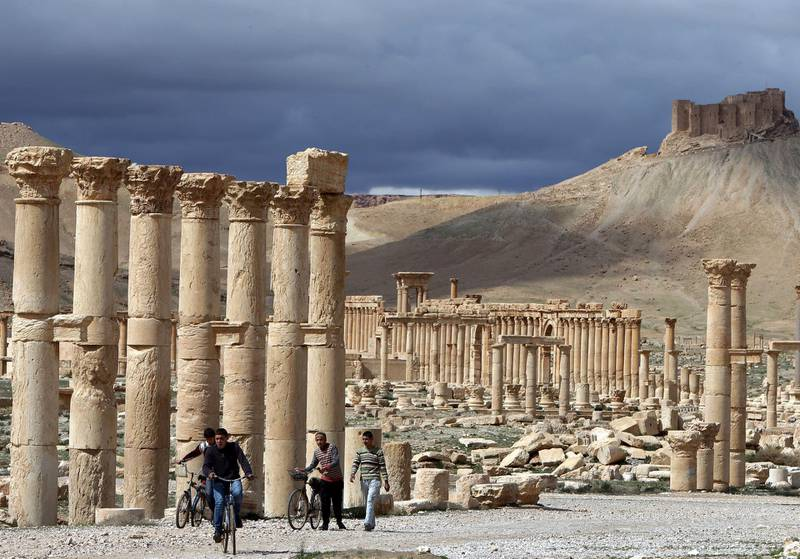 A picture taken on March 14, 2014 shows Syrian citizens riding their bicycles the ancient oasis city of Palmyra, 215 kilometres northeast of Damascus. From the 1st to the 2nd century, the art and architecture of Palmyra, standing at the crossroads of several civilizations, married Graeco-Roman techniques with local traditions and Persian influences. AFP PHOTO/JOSEPH EID / AFP PHOTO / JOSEPH EID