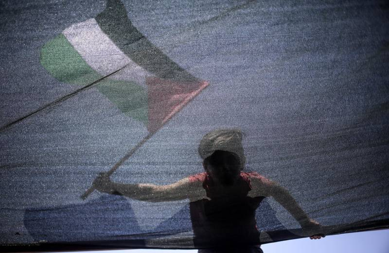epaselect epa06877784 A boy waves the Palestinian flag sailing in fishing boats carrying a group of activists during a protest against the Israeli siege imposed on Gaza Strip, west of Gaza City, 10 July 2018. According to media reports, a boat carrying students, wounded, and dual nationals in a symbolic attempt to break the Israeli blockade imposed for more than a decade, but was intercepted by the Israeli navy in the Mediterranean.  EPA/HAITHAM IMAD