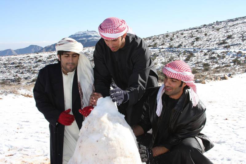 Caption RAK Ras Al Khaimah, UAE: 25 JANUARY 2009:  Snow covering the top of Jebel Jais Mountain and local men building a snow man during wintry weather in the Northern Emirate.    Coutesy Mike Charlton??Object Name:Rating:?Category:  Copyright:?Byline:Coutesy Mike CharltonCredit:?Headline: