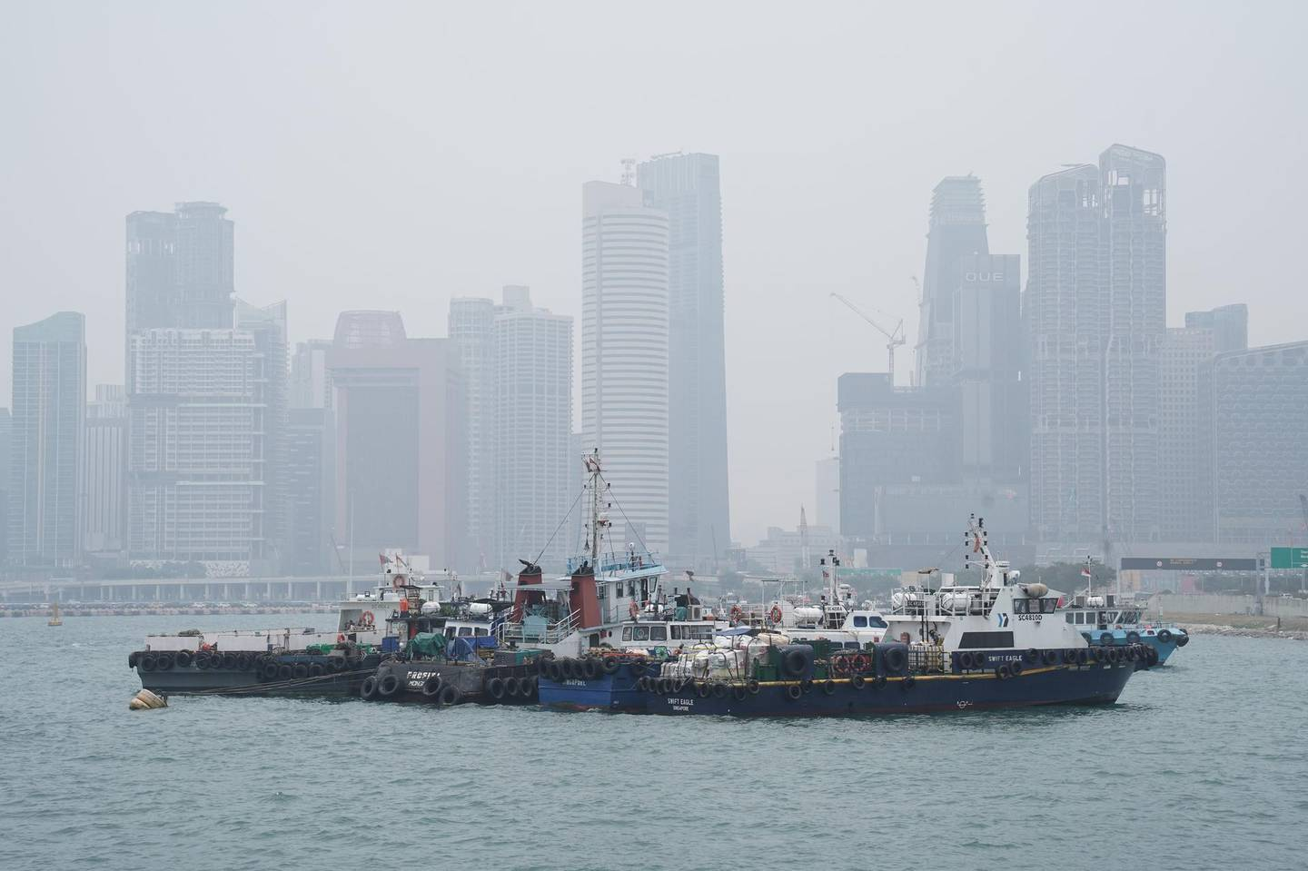 Buildings stand shrouded beyond anchored boats in Singapore, on Wednesday, Sept. 18, 2019. The air quality level in Singapore turned unhealthy ahead of the Formula 1 race this weekend, while Kuala Lumpur was ranked among the world's most polluted cities, as wind from neighboring Indonesia continued to sweep in ash and smoke from illegal burning of forests and farm land. Photographer: Dimas Ardian/Bloomberg