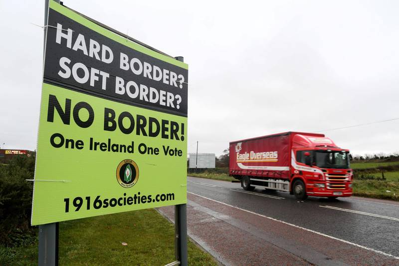 """(FILES) In this file photo taken on November 14, 2018, aA lorry passes a post-Brexit anti-border poster, outside Newry, Northern Ireland, near the border with Ireland.  Preparedness in Britain for a no-deal Brexit remains """"at a low level"""", with logjams at Channel ports threatening to impact drug and food supplies, according to government assessments released September 11, 2019. Britain's plan for no checks at the Irish border would likely """"prove unsustainable due to significant economic, legal and biosecurity risks"""", it said, adding that it could lead to a black market developing in border communities, with dissident groups expected to capitalise. Gibraltar could be particularly badly affected, it said, due to the imposition of checks at its border with Spain. / AFP / Paul FAITH"""