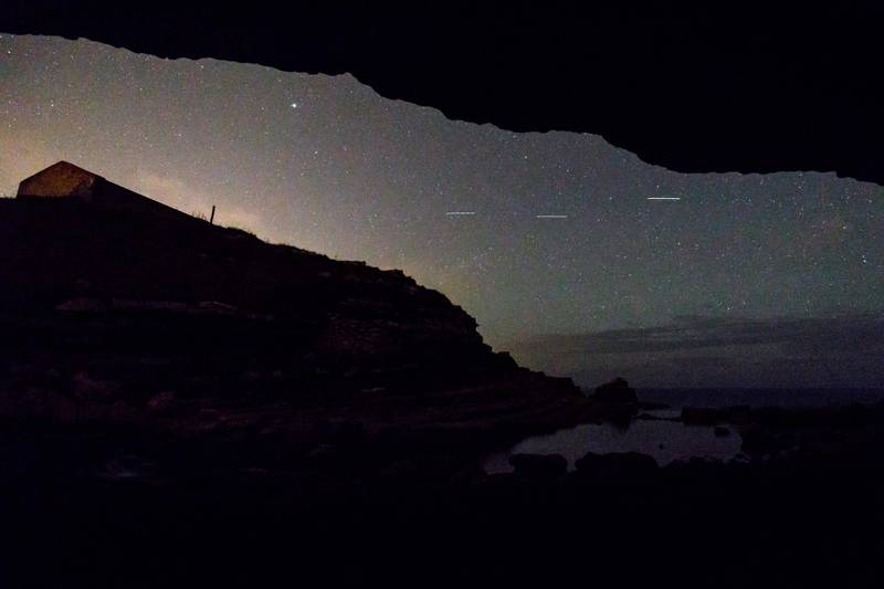 """This picture taken on August 12, 2017 shows a Perseid meteor along the Milky Way illuminating the dark sky near Comillas, Cantabria community, northern Spain, during the """"Perseids"""" meteor shower.  Northern hemisphere sky-gazers are in for a special treat on August 11 and 13, night with a rare shooting star """"outburst"""", which astronomers hope will not be marred by clouds and a bright Moon. / AFP PHOTO / CESAR MANSO"""