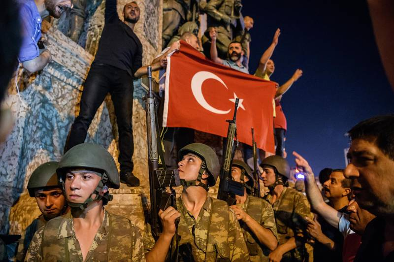 EDITORS NOTE: Graphic content / Turkish solders stay with weapons at Taksim square as people protest against the military coup in Istanbul on July 16, 2016. - Turkish military forces on July 16 opened fire on crowds gathered in Istanbul following a coup attempt, causing casualties, an AFP photographer said. The soldiers opened fire on grounds around the first bridge across the Bosphorus dividing Europe and Asia, said the photographer, who saw wounded people being taken to ambulances. (Photo by OZAN KOSE / AFP)