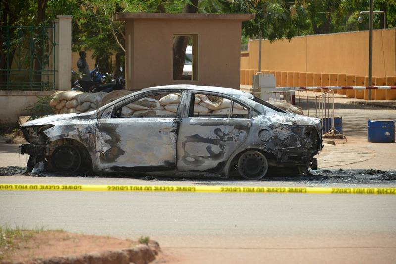 This photo taken on March 3, 2018 in Ouagadougou shows a burned car outside of the French embassy, a day after dozens of people were killed in twin attacks on the French embassy and the country's military. The government said the attack on the military was a suicide car bombing and that a planned meeting of the G5 Sahel regional anti-terrorism force may have been the target. / AFP PHOTO / Ahmed OUOBA