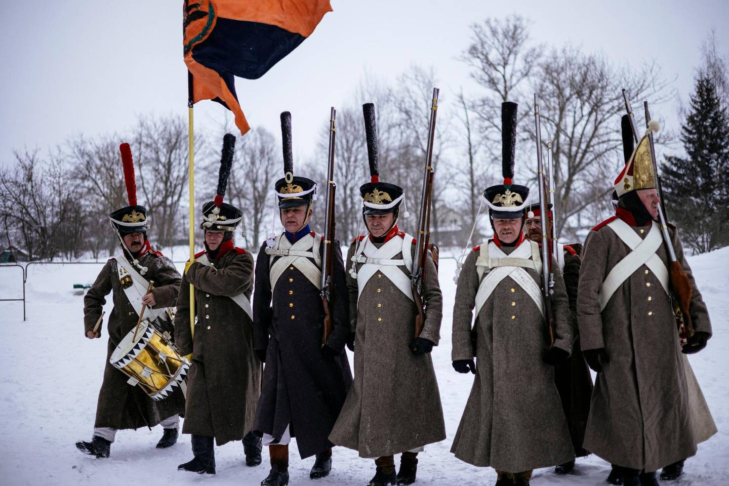 Re-enactors in period uniforms attend a burial ceremony of remains of Russian and French soldiers during a burial ceremony in the western town of Vyazma on February 13, 2021. Officials and descendants of 19th-century Russian and French military leaders gathered for a windswept ceremony in the western town of Vyazma to re-bury the remains of 126 people killed in one of the bloodiest battles of Napoleon's Russian campaign. / AFP / Dimitar DILKOFF