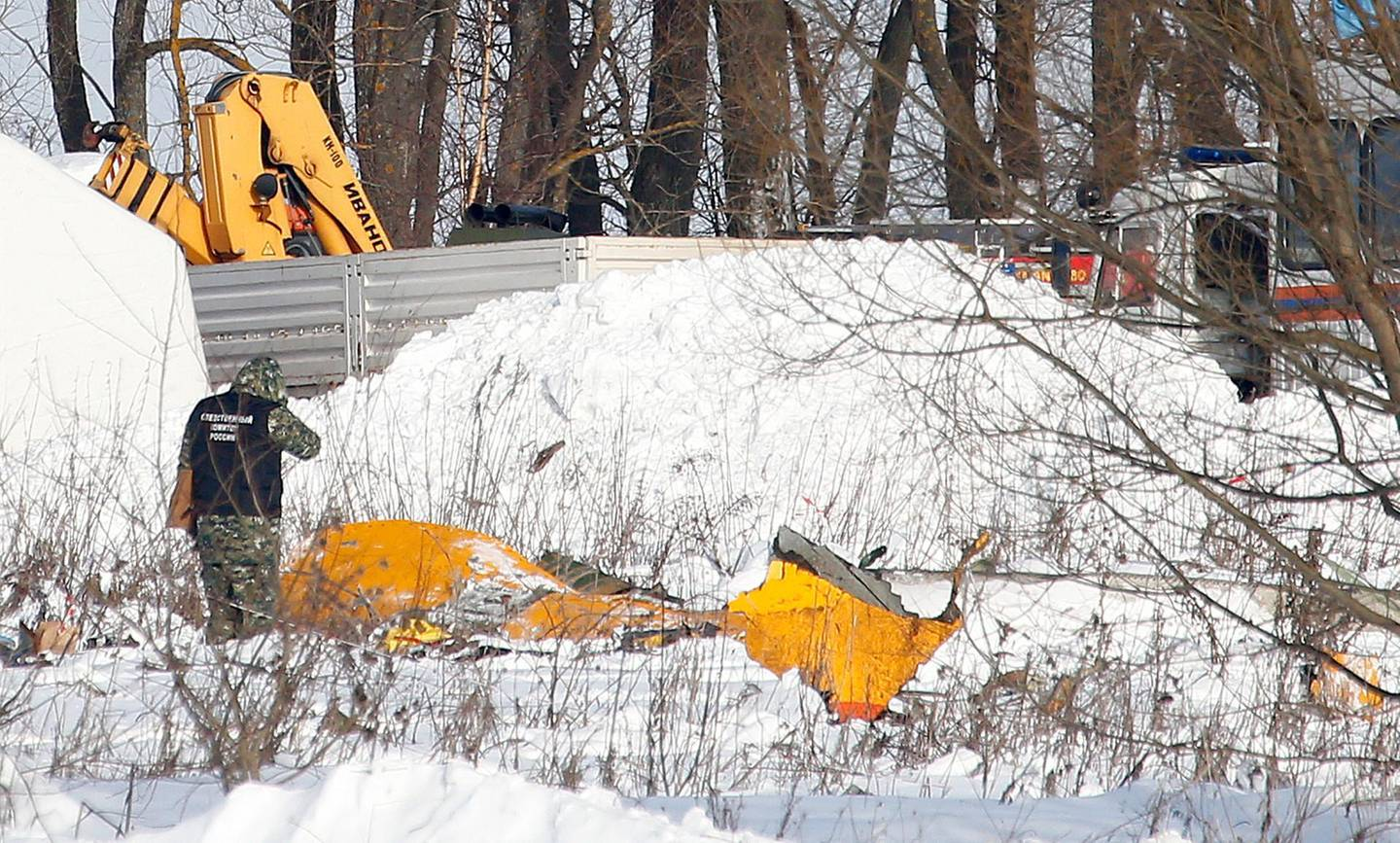 A man looks at wreckage near the scene of a AN-148 plane crash in Stepanovskoye village, about 40 kilometers (25 miles) from the Domodedovo airport, Russia, Monday, Feb. 12, 2018. A Russian passenger plane carrying 71 people crashed Sunday near Moscow, killing everyone aboard shortly after the jet took off from one of the city's airports. The Saratov Airlines regional jet disappeared from radar screens a few minutes after departing from Domodedovo Airport en route to Orsk, a city some 1,500 kilometers (1,000 miles) southeast of Moscow. (AP Photo/Alexander Zemlianichenko)