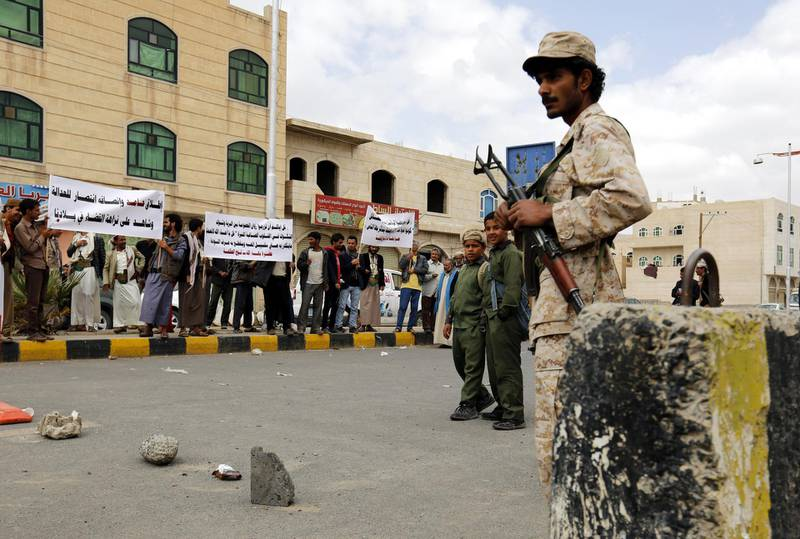 epa05242653 A Yemeni soldier (R) keeps watch as Baha'i Faith members hold banners during a protest against the trial of member of the Baha'i Faith Hamed Haydara, outside the state security court in Sana?a, Yemen, 03 April 2016. According to reports, Yemeni authorities have indicted Hamed Haydara, a Yemeni national who was detained in December 2013 accused of being a spy for Israel and converting Muslims to the Baha'i Faith.  EPA/YAHYA ARHAB