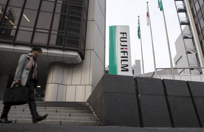 A pedestrian walks past a Fujifilm Holdings Corp. logo displayed outside one of the company's offices in Tokyo, Japan, on Wednesday, Jan. 31, 2018. Fujifilm Holdings is gaining control of Xerox Corp. in a deal that would create an $18 billion company and see the iconic American corporate giant launching into new lines of business to seek global growth. Photographer: Tomohiro Ohsumi/Bloomberg