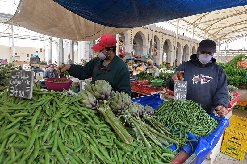 A Tunisian vendor, wearing a protective mask, weighs vegetables at a stall in a central market in the capital Tunis on April 24, 2020, during the first day of the Muslim holy month of Ramadan, after authorities partially eased the lockdown measures. (Photo by FETHI BELAID / AFP)