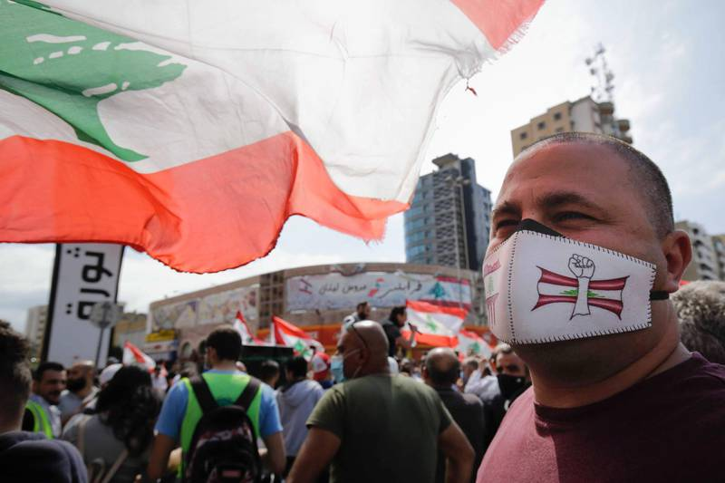 A protester wearing a face mask with an illustration depicting a raised fist before a Lebanese flag looks on as he attends a demonstration against dwindling economic conditions in the country, at al-Nour Square in the centre of the northern port city of Tripoli on May 3, 2020.  / AFP / Ibrahim CHALHOUB