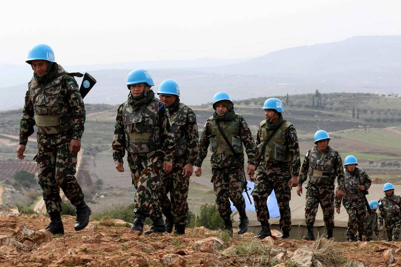 """A picture taken from the southern Lebanese village of Meiss al-Jabal on December 16, 2018, shows United Nations Interim Forces in Lebanon (UNIFIL) soldiers patroling on the Lebanese side of the border with Israel.  Israel's army said it has uncovered another Hezbollah """"attack tunnel"""" leading from Lebanon into its territory, the fourth since it started a search-and-destroy operation this month. / AFP / Mahmoud ZAYYAT"""