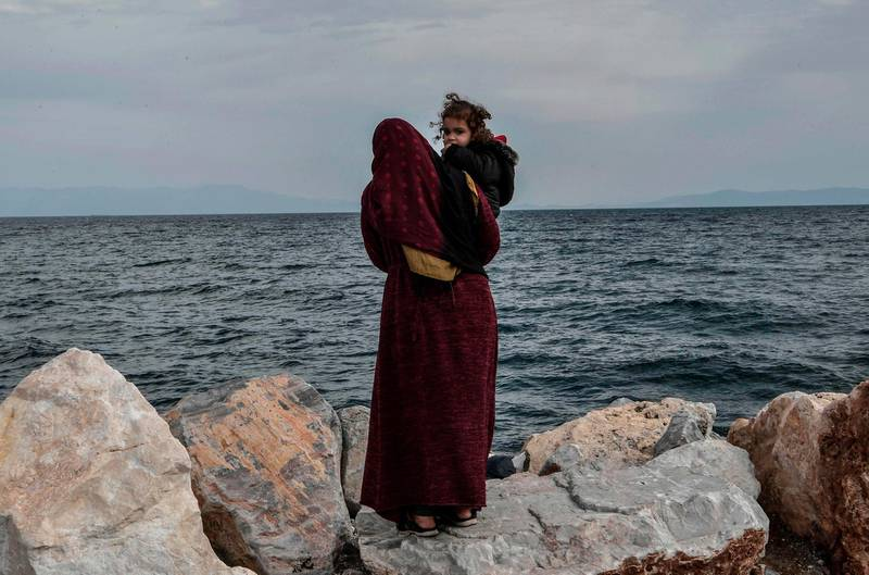 A refugee mother holds her child  as she stands looking out at sea at he port of Mytilene on the Greek Island of Lesbos on March 7, 2020, close to where a Greek military carrier is being used to accomodate refugees and migrants who arrived on the island after March 1, 2020.   / AFP / LOUISA GOULIAMAKI