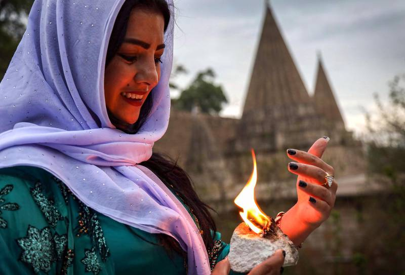 An Iraqi Yazidi woman holds a candle outside the Temple of Lalish, in a valley near the Kurdish city of Dohuk about 430 kilometres northwest of the capital Baghdad, on April 16, 2019, during a ceremony marking the Yazidi New Year. Of the 550,000 Yazidis in Iraq before the Islamic State (IS) group invaded their region in 2014, around 100,000 have emigrated abroad and 360,000 remain internally displaced. Roughly 3,300 Yazidis have returned from IS captivity in the last five years, only 10 percent of them men. / AFP / SAFIN HAMED