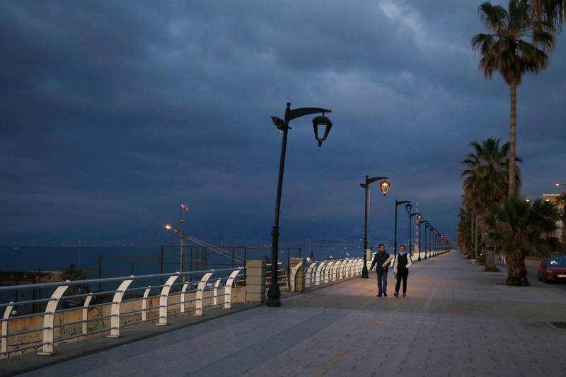 A couple walks at Beirut's seaside corniche, or waterfront promenade, along the Mediterranean Sea, which is almost empty of residents and tourists in Beirut, Lebanon, Saturday, March 21, 2020. Lebanon has been taking strict measures to limit the spread of the coronavirus closing restaurants and nightclubs as well as schools and universities. For most people, the new coronavirus causes only mild or moderate symptoms. For some it can cause more severe illness. (AP Photo/Bilal Hussein)