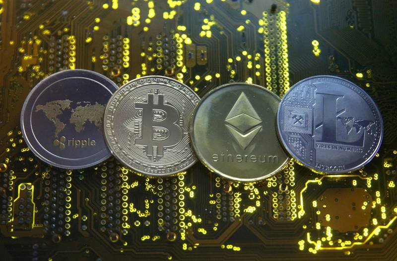 FILE PHOTO: Representations of the Ripple, Bitcoin, Etherum and Litecoin virtual currencies are seen on a PC motherboard in this illustration picture, February 14, 2018. REUTERS/Dado Ruvic/Illustration/File Photo