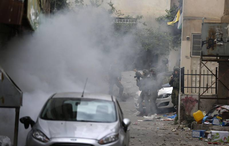Israeli troops fire tear gas as they clash with Palestinian youth in the Amari refugee camp near Ramallah in the occupied West Bank after they stormed the camp on May 28, 2018.  Israeli troops raided the camp in the early morning hours after Sergeant Ronen Lubarsky, 20, of the Duvdevan special forces unit, reportedly died on May 26, two days after being struck on the head by a stone block thrown during an arrest raid. Israeli media said that the block was a granite slab dropped from a third-floor window. / AFP / ABBAS MOMANI