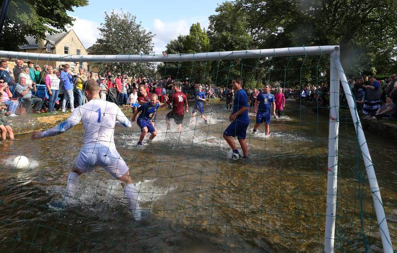 BOURTON-ON-THE-WATER, ENGLAND - AUGUST 27: Players from Bourton Rovers compete against each other  during the annual Bourton-on-the-Water Football Match played on the River Windrush on August 27, 2018 in Bourton-on-the-Water, England. (Photo by Catherine Ivill/Getty Images)