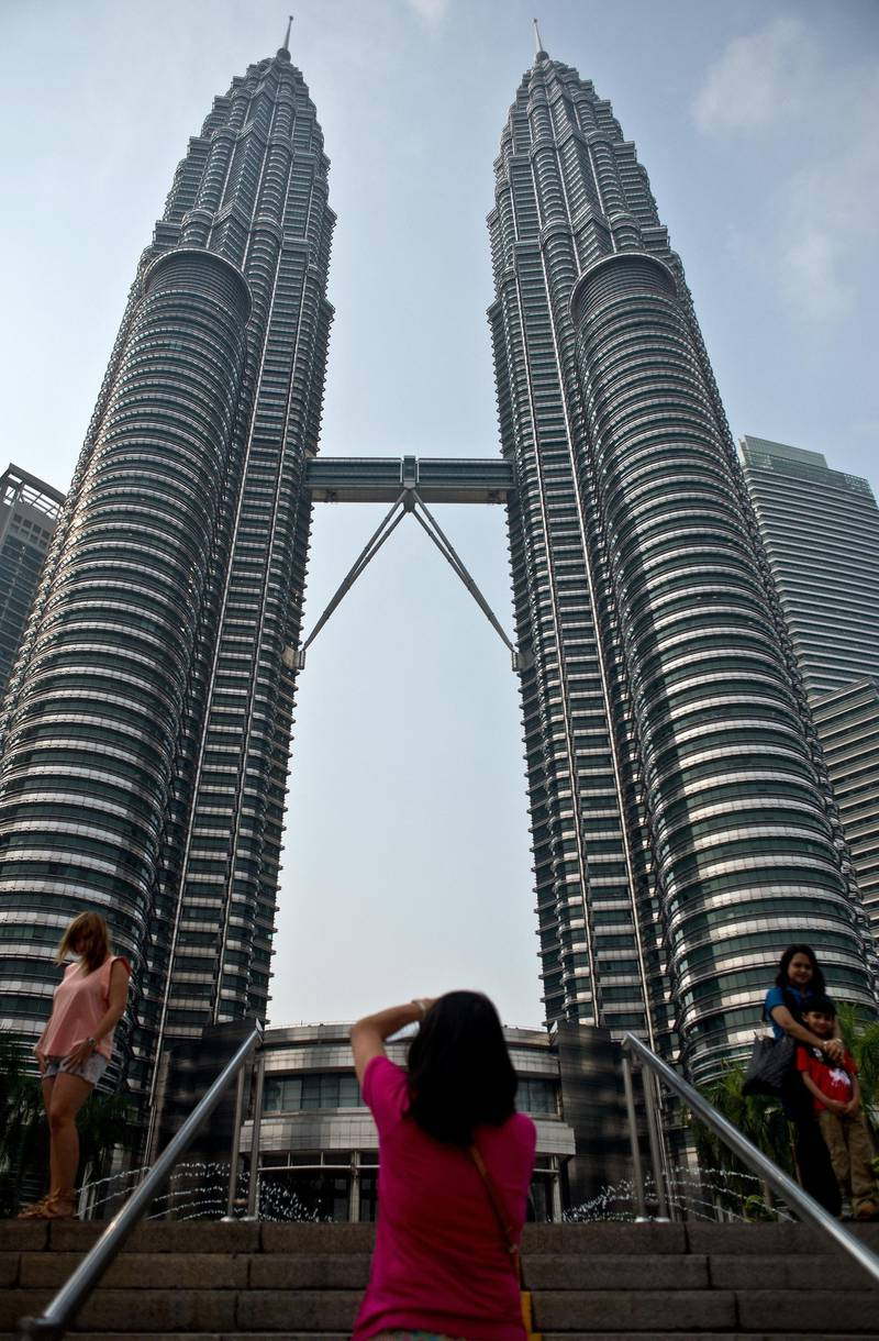 To go with Ukraine-Russia-crisis-aviation-Malaysia-tourism,FOCUS by Bhavan Jaipragas Tourists pose at the Petronas Twin Towers in Kuala Lumpur on July 23, 2014. An unprecedented second major aviation disaster in four months could further associate Malaysia with calamity in the eyes of travellers, observers warn, putting the tropical destination's vital tourism sector at risk. AFP PHOTO/ MANAN VATSYAYANA (Photo by MANAN VATSYAYANA / AFP)