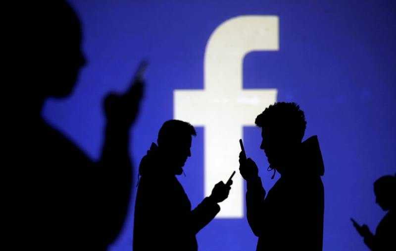 FILE PHOTO: Silhouettes of mobile users are seen next to a screen projection of Facebook logo in this picture illustration taken March 28, 2018.  REUTERS/Dado Ruvic/Illustration/File Photo