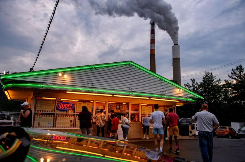 CHESWICK, PA - JUNE 07: People line up for ice cream at Glens Custard in the shadow of GenOns Cheswick Power Station, which still burns coal to produce 637 megawatts of electricity for the region on June 7, 2021 about 15 miles northeast of Pittsburgh in Cheswick, Pennsylvania. Scientists from Scripps Institution of Oceanography and the National Oceanic and Atmospheric Administration reported today that despite a year-long pause in much of the economy due to the Covid-19 pandemic, levels of atmospheric carbon dioxide reached the highest levels since accurate measurements began 63 years ago, according to published reports.   Jeff Swensen/Getty Images/AFP == FOR NEWSPAPERS, INTERNET, TELCOS & TELEVISION USE ONLY ==