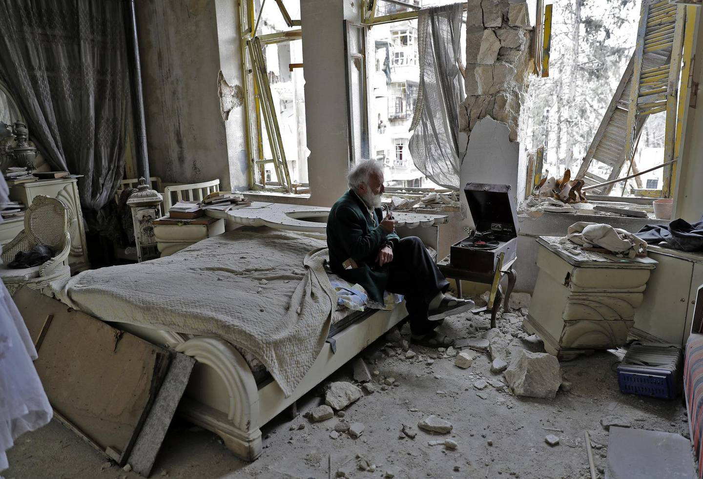 Mohammed Mohiedin Anis, or Abu Omar, 70, smokes his pipe as he sits in his destroyed bedroom listening to music on his vinyl player, gramophone, in Aleppo's formerly rebel-held al-Shaar neighbourhood. (Photo by JOSEPH EID / AFP)