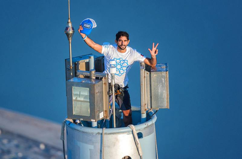 """An image made available on November 28, 2013 by the personal photographer Sheikh Hamdan Bin Mohamed Bin Rashid al-Maktoum, shows Dubai's Crown Prince Sheikh Hamdan, gesturing as he wears a t-shirt bearing the logo of Dubai's 2020 World Expo campaign on top of Burj Khalifa, the world's tallest tower on November 25, 2013 to mark the emirates 42nd independence day and as part of a campaign that Dubai launched to win the 2020 World Expo. Dubai beat off opposition from Brazil, Russia and Turkey on November 27, to win the right to host the 2020 World Expo, sparking celebrations in the Gulf city and a stunning fireworks display at the world's tallest building. AFP PHOTO/HO/ALI ISSA-PERSONAL PHOTOGRAPHER OF SHIEKH HAMDAN BIN MOHAMED BIN RASHID AL-MAKTOUM   == RESTRICTED TO EDITORIAL USE - MANDATORY CREDIT """"AFP PHOTO / ALI ISSA-PERSONAL PHOTOGRAPHER OF SHIEKH HAMDAN BIN MOHAMED BIN RASHID AL-MAKTOUM"""" - NO MARKETING NO ADVERTISING CAMPAIGNS - DISTRIBUTED AS A SERVICE TO CLIENTS == (Photo by ALI ISSA / ALI ISSA / AFP)"""