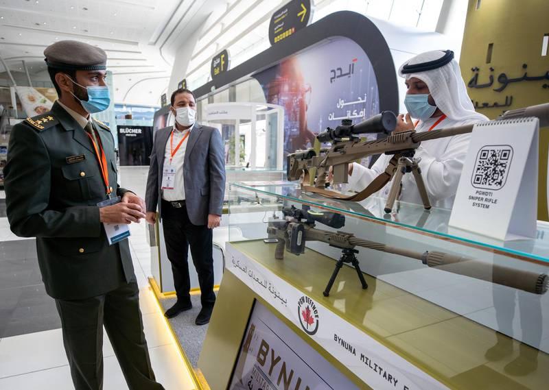 Abu Dhabi, United Arab Emirates, February 24, 2021.  Idex 2021 Day 4.   A UAE officer looks at the UAE made PGWDTI  Bynuna Sniper Rifle System.Victor Besa / The NationalSection:  NA