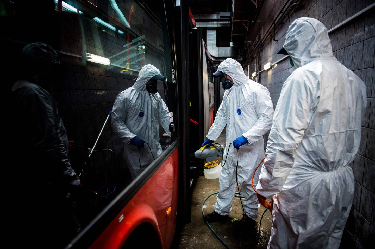 Workers wearing protective clothes disinfect an interior of a public bus in a bus-wash station at Transport Company of Bratislava city as part of precautionary measures against the spread of the new coronavirus COVID-19 in Bratislava, Slovakia on March 11, 2020. Many schools were closed and public events were cancelled due to the coronavirus outbreak in Slovakia as first seven cases of infection were confirmed. / AFP / VLADIMIR SIMICEK