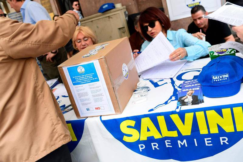 """People gather at the stand of far-right party """"Lega"""" (League) to approve a proposal of common governmental program with the Five Star Movement, in center Milan, on May 20, 2018. The anti-establishment Five Star Movement (M5S) and far-right League party should meet Italy's President Sergio Mattarella tomorrow in Rome and reveal the name of their Prime Minister.  / AFP / MIGUEL MEDINA"""