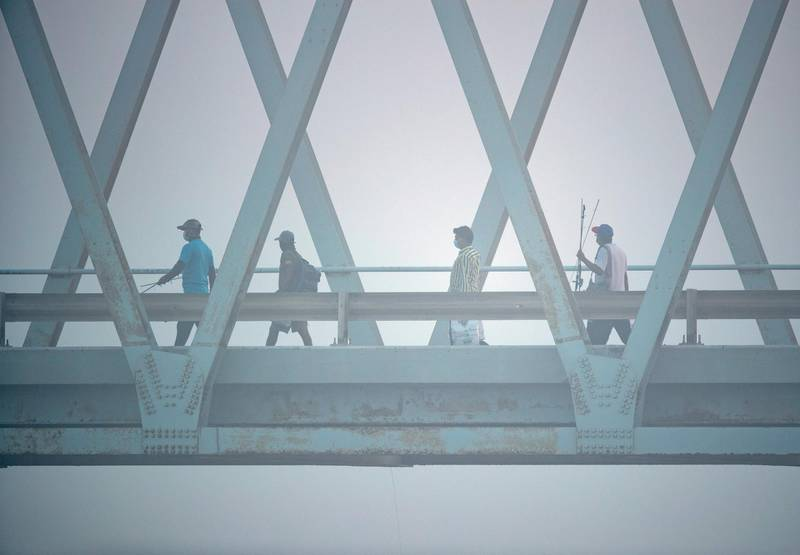 Anglers cross the Yas Iron Bridge in Abu Dhabi to get to their fishing spot amidst the fog on June 4th, 2021. Victor Besa / The National.