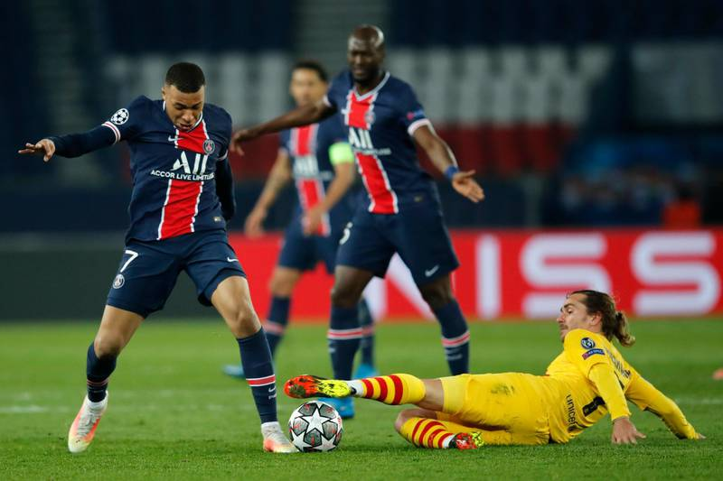 PSG's Kylian Mbappe, left, fights for the ball with Barcelona's Antoine Griezmann during the Champions League, round of 16, second leg soccer match between Paris Saint-Germain and FC Barcelona at the Parc des Princes stadium in Paris, Wednesday, March 10, 2021. (AP Photo/Christophe Ena)