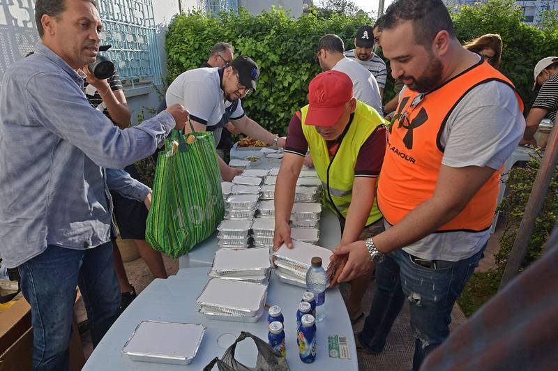 Tunisian volunteers distribute free Iftar meals on May 7, 2020 at the Ariana near Tunis during the Muslim holy fasting month of Ramadan. - Mosques in Algeria, Morocco and Tunisia have been closed to curb the spread of the novel coronavirus Covid-19, preventing special evening prayers. (Photo by FETHI BELAID / AFP)