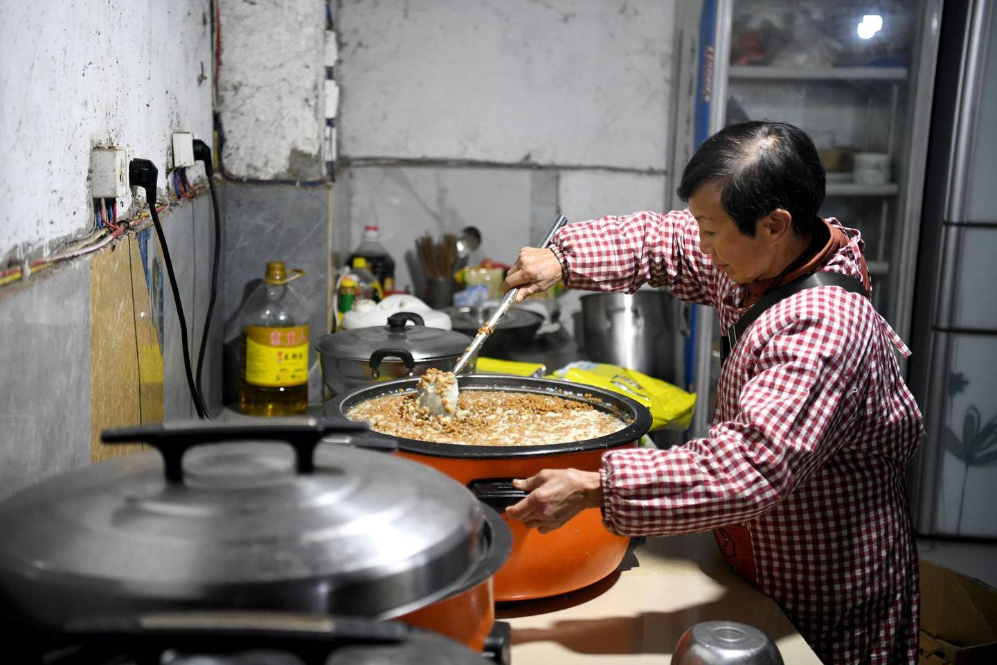 This photo taken on November 29, 2020 shows Wen Junhong preparing dog food at a home for rescued animals in Chongqing, southwestern China.     Twenty years ago, Wen Junhong saved an abandoned dog from the streets of Chongqing in southwestern China. She now shares her home with more than 1,300 of them, and they keep on coming.  - TO GO WITH AFP STORY CHINA-ANIMAL-RESCUE,FOCUS BY HELEN ROXBURGH AND QIAN YE  / AFP / NOEL CELIS / TO GO WITH AFP STORY CHINA-ANIMAL-RESCUE,FOCUS BY HELEN ROXBURGH AND QIAN YE