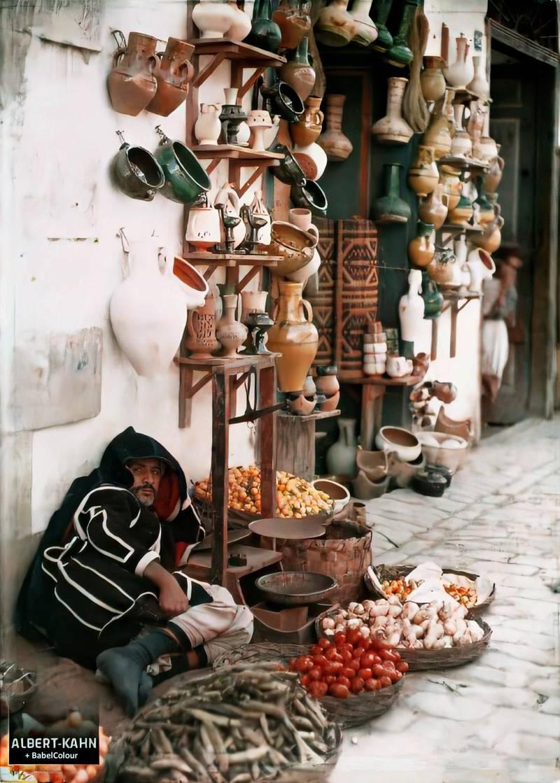Un marchand de fruits et légumes devant une boutique de poteries dans un souk de la médina, Tunis, Tunisie, 1909 ou 1910 ou 1911, (Autochrome, 12 x 9 cm),  Jules Gervais-Courtellemont, Département des Hauts-de-Seine, musée Albert-Kahn, Archives de la Planète, A 30