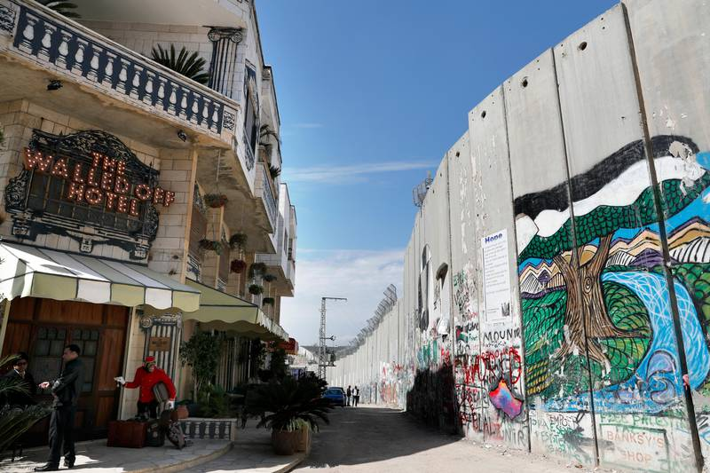 The Israeli controversial separation wall is seen in front of artist Banksy's newly opened Walled Off hotel in the Israeli occupied West Bank town of Bethlehem, on March 15, 2017.  Secretive British street artist Banksy opened a hotel next to Israel's controversial separation wall in Bethlehem on Friday, his latest artwork in the Palestinian territories. / AFP PHOTO / THOMAS COEX